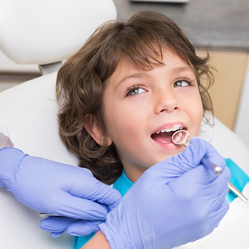 Dentist checking child's tooth-colored fillings