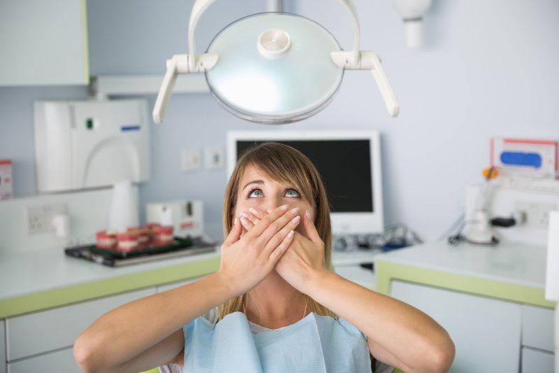 Woman with dental phobia covering her mouth at the dentist