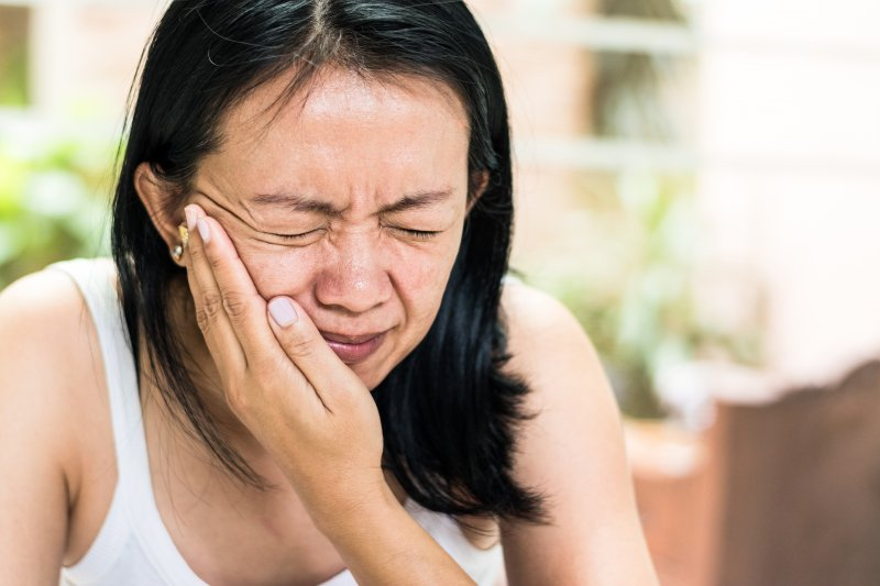 Woman holding cheek and in need of an emergency dentist